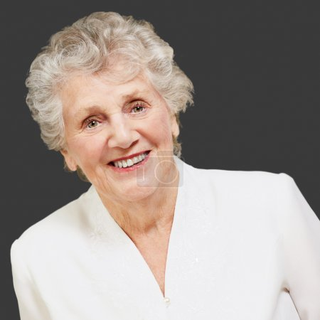 Photo for Portrait of a senior woman smiling on grey background - Royalty Free Image