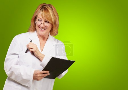 Photo for Female doctor holding book isolated on green background - Royalty Free Image