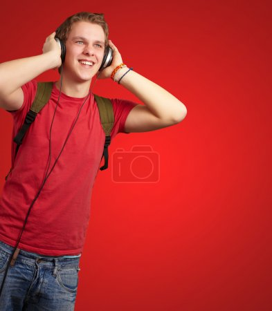 portrait of cheerful young student listening music with headphon