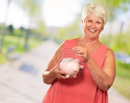 Senior Woman Holding A Piggybank