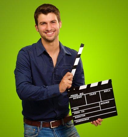 Photo pour Un jeune homme tenant un clapet sur fond vert - image libre de droit