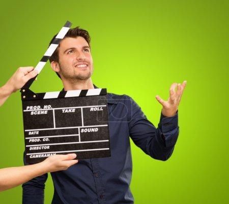 Photo pour Un jeune homme tenant un clapet et agissant sur fond blanc - image libre de droit