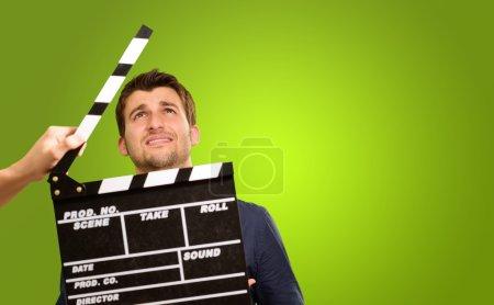 Photo pour Un jeune homme tenant un clapet et agissant sur fond vert - image libre de droit