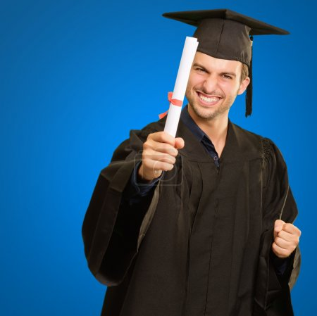 Photo for Graduate Man Holding Degree Isolated On Blue Background - Royalty Free Image