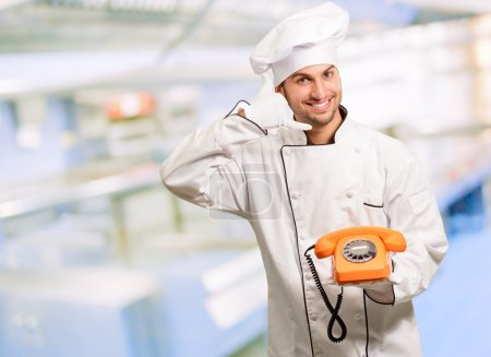 Portrait Of A Chef Holding Telephone And Making Call Sign