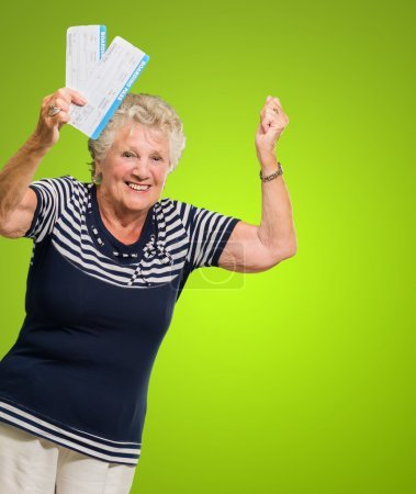 Photo for Portrait Of Senior Woman Holding Boarding Pass Cheering On Green Background - Royalty Free Image