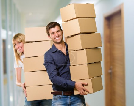 Photo for Man And Woman Holding Stack Of Cardboard, Indoor - Royalty Free Image