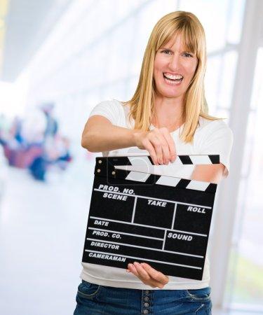 Photo pour Happy Woman Holding Clapper Board, intérieur - image libre de droit