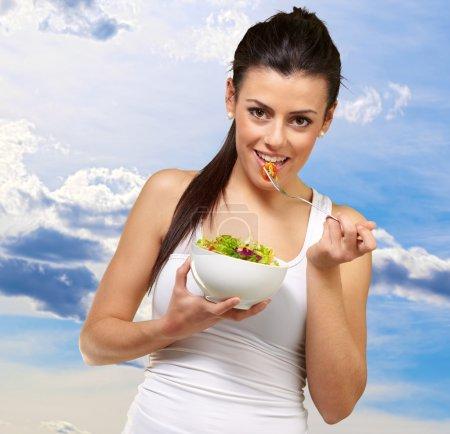 Photo pour Jeune femme tenant et mangeant de la salade, extérieur - image libre de droit