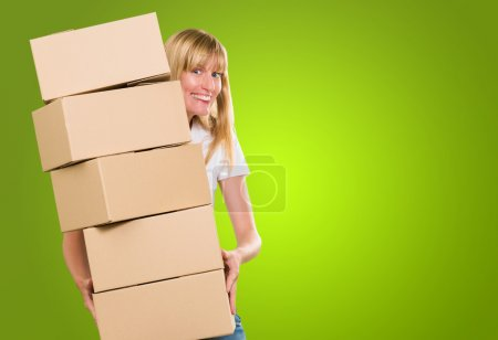Photo for Woman holding a pile of boxes against a green background - Royalty Free Image