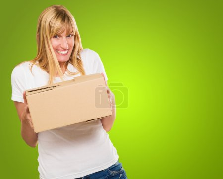 Photo for Woman Holding Cardboard box against a green background - Royalty Free Image