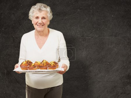 portrait of senior woman showing homemade muffins against a grun