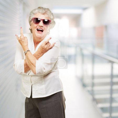 Photo for Portrait of senior woman smiling and wearing sunglasses at modern office - Royalty Free Image