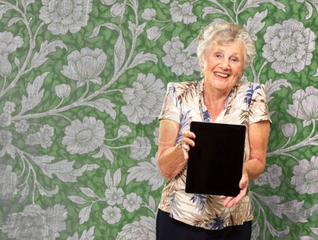 Photo for Portrait Of A Senior Woman Holding A Digital Tablet, Indoor - Royalty Free Image