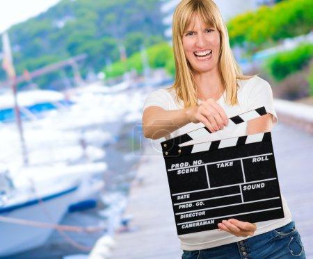Photo pour Happy Woman Holding Clapper Board dans un port - image libre de droit
