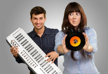 Young Girl Showing Vinyl Against Young Man Holding Piano