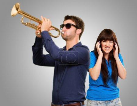 Photo pour L'homme de soufflage trompette devant une femme frustrée sur fond gris - image libre de droit