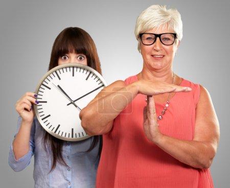 Photo pour Femme âgée montrant Timeout signe en face de la jeune femme tenant horloge sur fond gris - image libre de droit