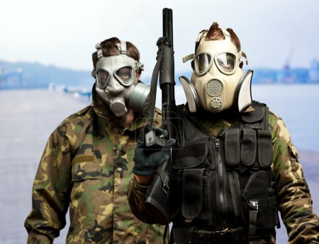 Portrait Of Soldiers With Gun And Gas Mask