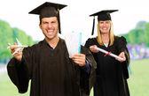 Portrait de deux étudiants diplômés heureux