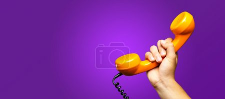 Photo for Close Up Of Hand Holding Telephone against a purple background - Royalty Free Image