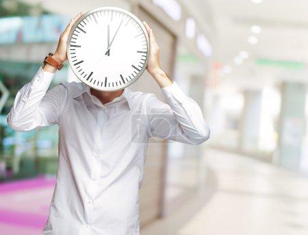 Photo pour Jeune homme tenant une grande horloge couvrant son visage, intérieur - image libre de droit