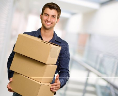 Young Man Holding Stack Of Cardboxes