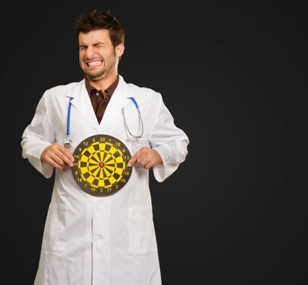 Scared Young Doctor Holding Bulls Eye