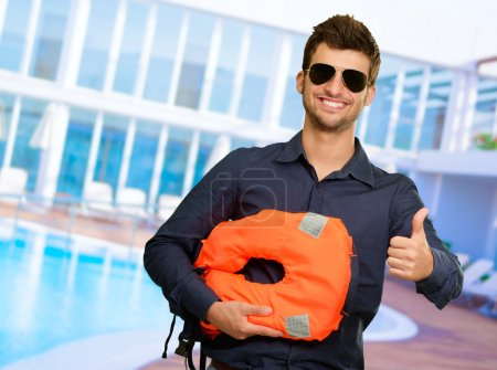 Happy Young Man Holding Life Jacket And Showing Thumb Up Sign