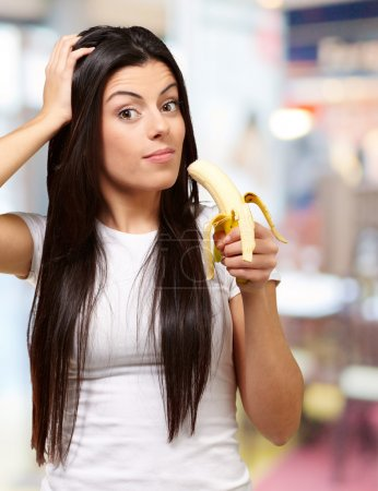 A Young Woman Holding A Banana