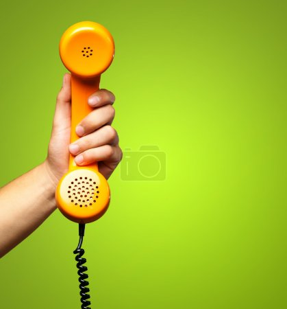 Photo for Close Up Of Hand Holding Telephone against a green background - Royalty Free Image