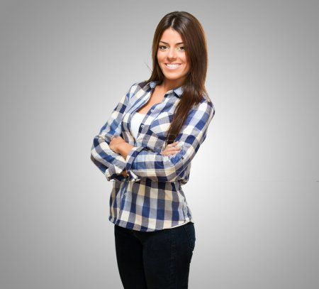 Photo for Portrait Of A Young Woman With Arms Folded against a grey background - Royalty Free Image