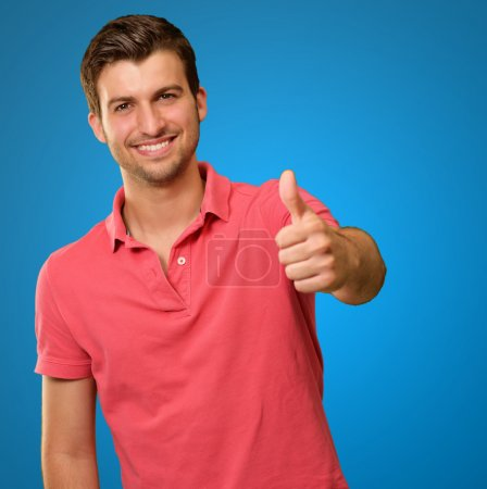 junger Mann lächelt mit erhobenem Daumen