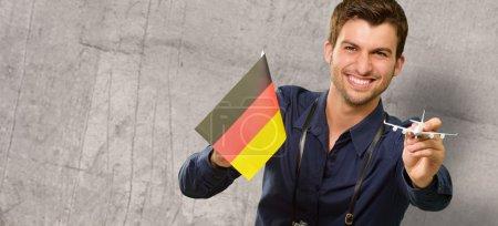Photo pour Photographe tenant un drapeau allemand et un avion miniature, intérieur - image libre de droit
