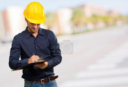 Portrait Of Architect Writing On Clipboard