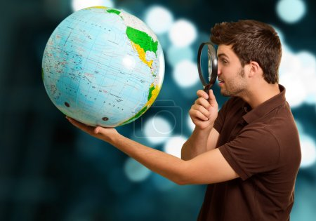 Man Looking Through Magnifying Glass At Globe