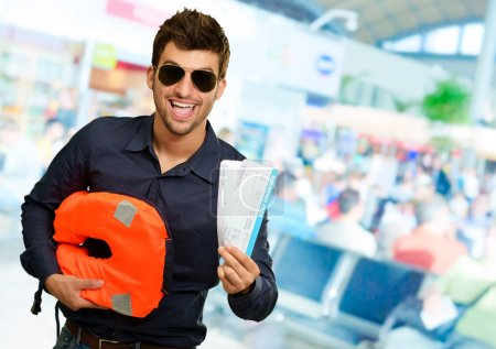 Happy Man Holding Life Jacket And Boarding Pass