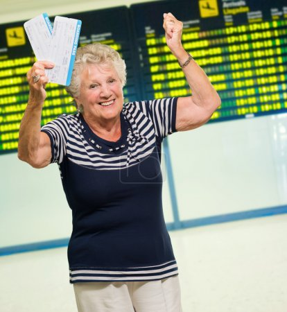 Photo for Happy Senior Woman Holding Boarding Pass, Indoors - Royalty Free Image