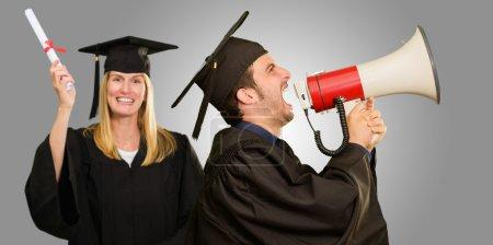 Photo pour Étudiant diplômé tenant mégaphone et certificat sur fond gris - image libre de droit