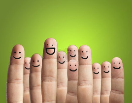 Photo pour Close-up Of Fingers With Smiley Faces On Green Backgroun - image libre de droit
