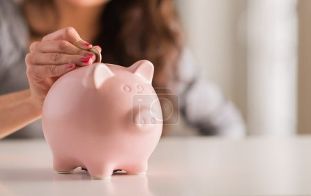 Photo for Woman Putting Coin In Piggy Bank, Indoor - Royalty Free Image