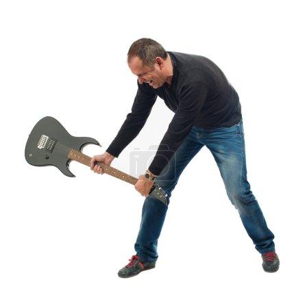 Photo pour Portrait d'un homme mature frapper guitare sur fond blanc - image libre de droit