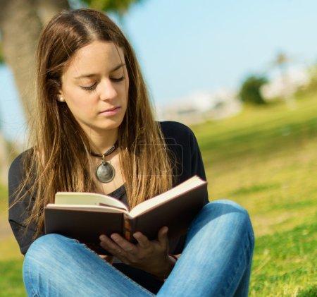 Photo pour Jeune femme lisant un livre dans le parc, en plein air - image libre de droit