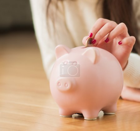 Woman's Hand Putting Coin In Piggybank