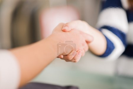Photo pour Gros plan de deux femmes serrant la main, à l'intérieur - image libre de droit
