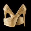 Crystals encrusted gold pair of shoes isolated on ...