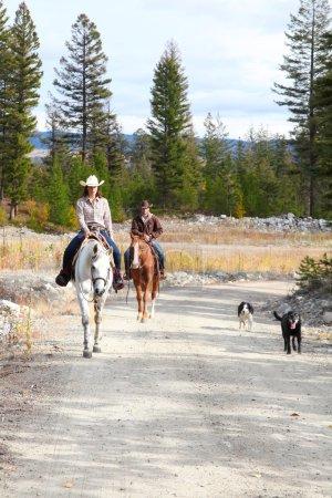 Photo pour Belle brune cow-boy et cow-girl sur un sentier de montagne - image libre de droit
