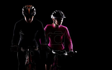 Photo for Low key silhouette of a man and a girl cyclists riding bicycles on black background - Royalty Free Image