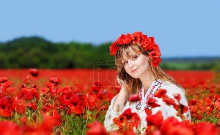 Photo pour Belle fille qui porte la robe brodée traditionnelle ukrainienne et bandeau pavot debout dans un champ de pavot - image libre de droit