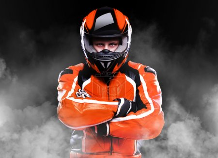 Photo for Closeup portrait of a biker in orange equipment and helmet on black background - Royalty Free Image